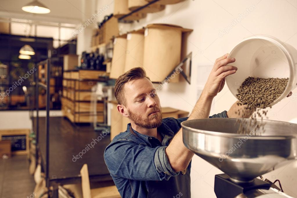man pouring coffee beans in machine