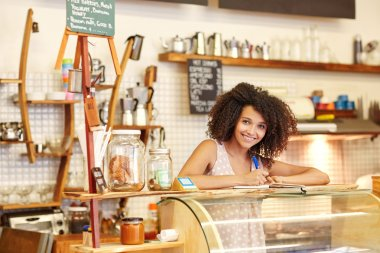 woman with at coffee counter writing an order