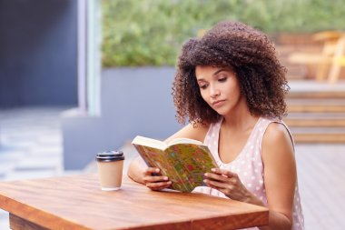 woman reading book with takeaway coffee
