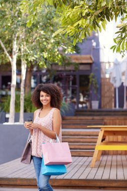 Three quarter length shot of a pretty mixed race woman standing outdoors holding a takeaway coffee and bags of shopping stock vector