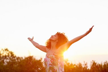 Woman with outstretched arms on summer evening