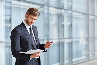 businessman holding cell phone and documents