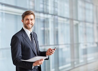 businessman smiling and holding phone and notes