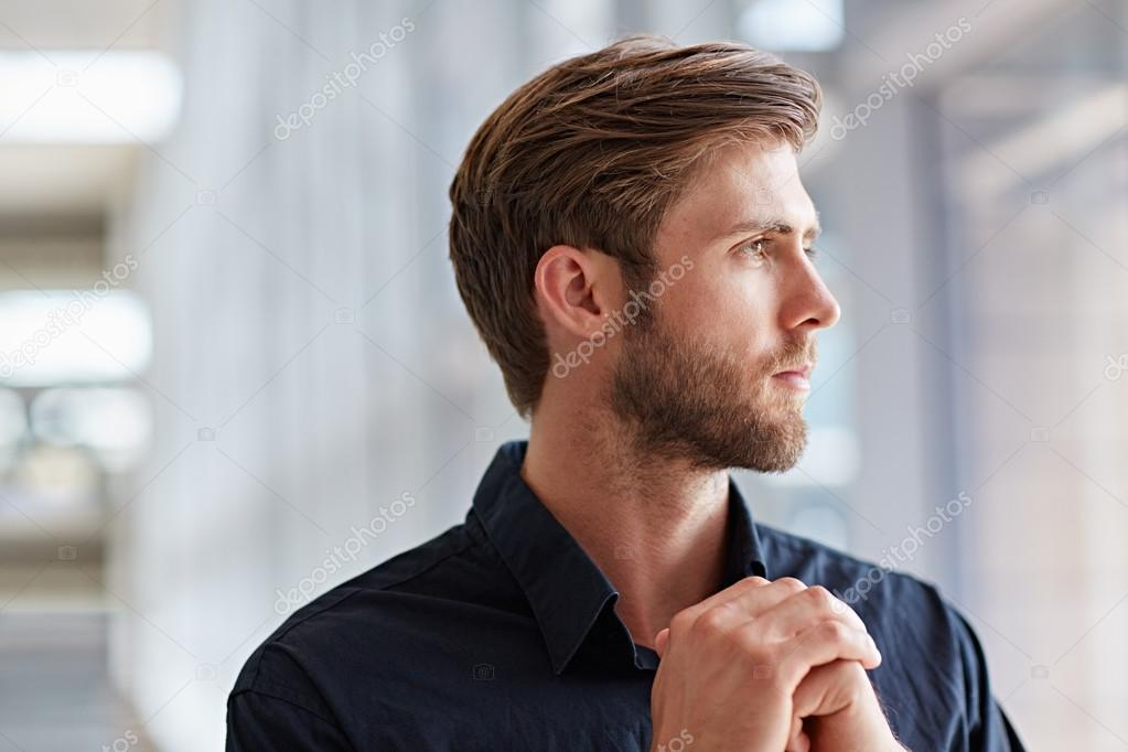 businessman looking up thoughtfully and confidently