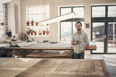 designer standing in workshop with cup of coffee