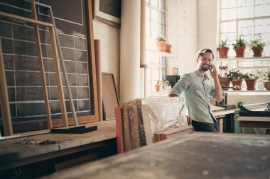 business owner on talking on phone in workshop