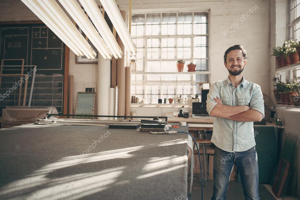 designer standing in studio with arms crossed