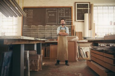 craftsman in workshop with arms folded