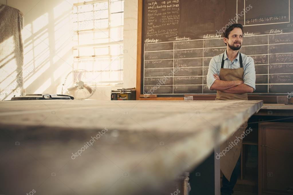 Craftsman looking away with arms crossed