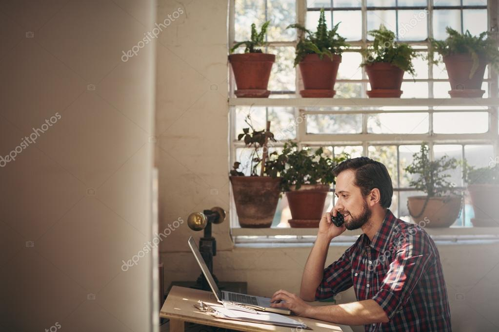 entrepreneur using phone and working on laptop