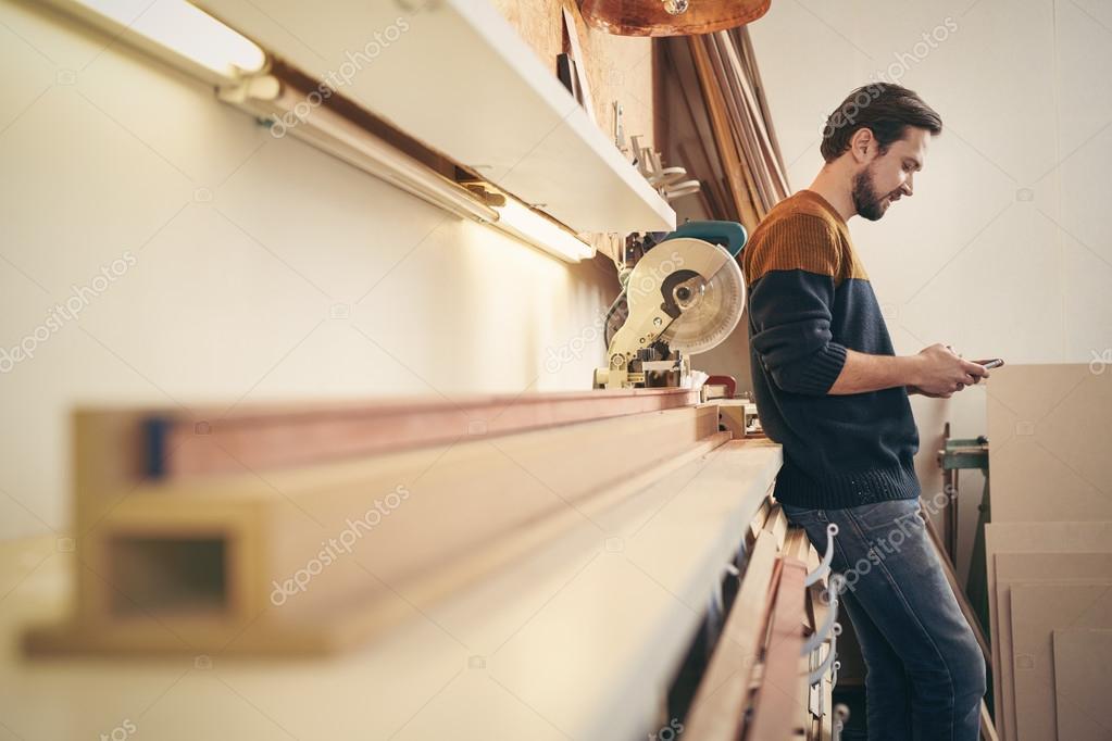 craftsman using phone in workshop