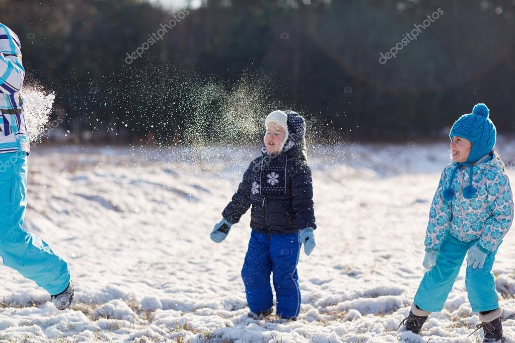 Two kids throwing snowballs at mother