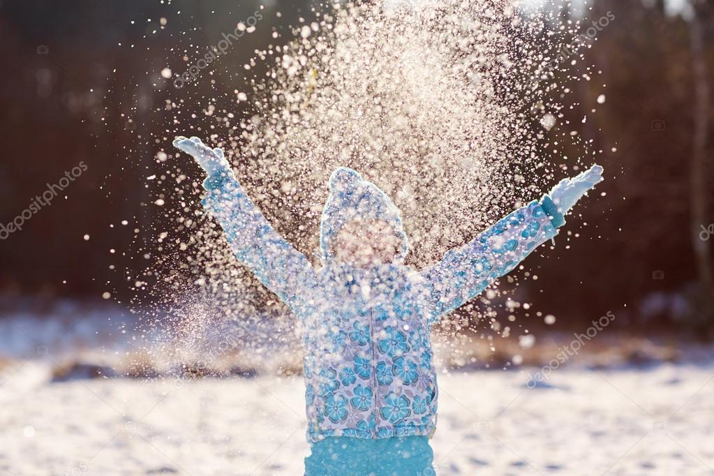 girl throwing handful of snow in air