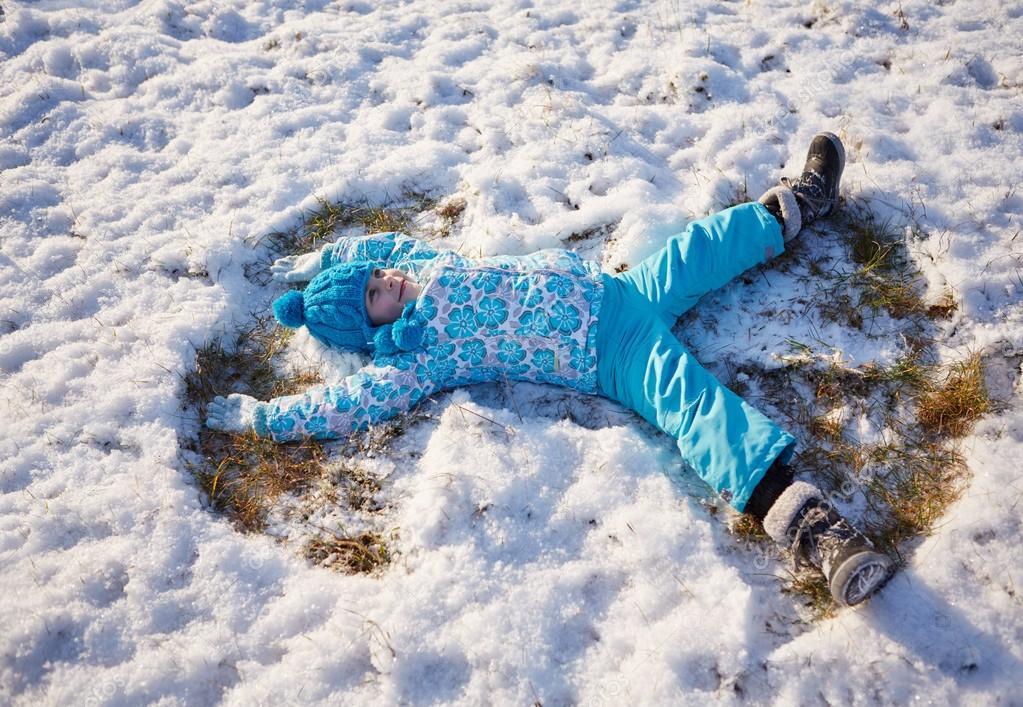 girl making snow angels