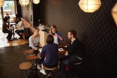 Friends having meeting in coffee shop