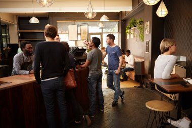 People standing at counter of coffee shop