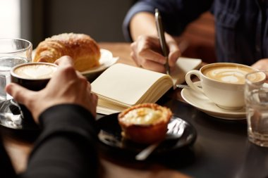 Interview in cafe with coffee and pastry. Cropped image of two hands at a table with coffee and pastry snacks while the other is writing in a notebook stock vector