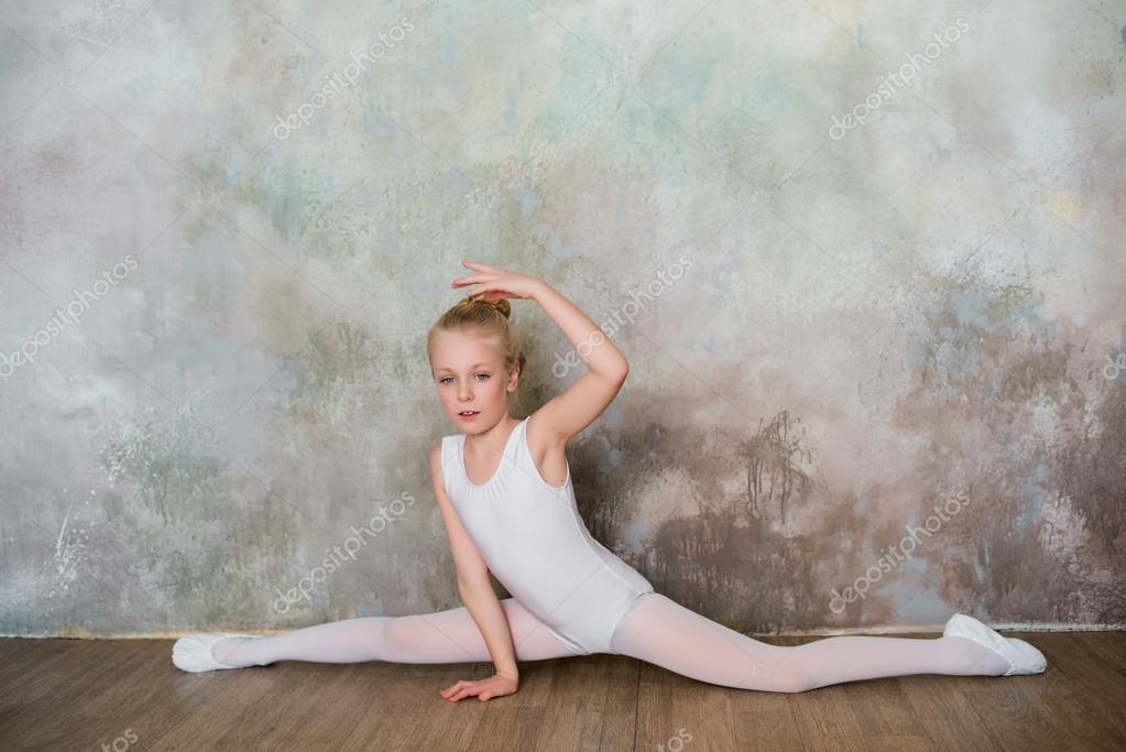 308aa67741 Pequena bailarina sentada sobre o racha no maiô branco — Fotografia de Stock