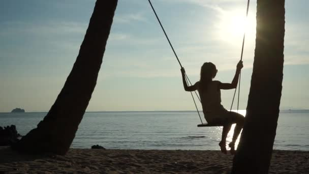 Young woman on a swing at the tropical beach against the sea