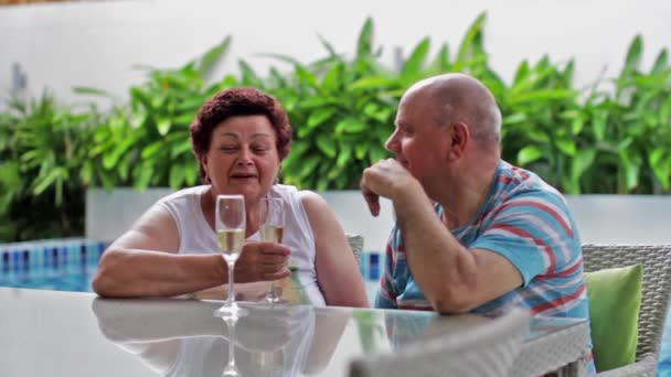 Glücklich lächelnde ältere paar trinken Champagner in eine tropische Villa am Pool