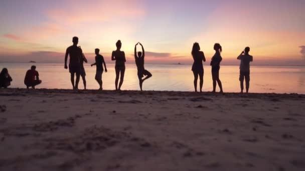 Menschen spazieren am Strand und genießen den bunten Sonnenuntergang.