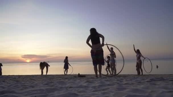 Silhouette einer jungen Frau, die mit Hula-Hoop-Reifen am Strand bei Sonnenuntergang tanzt. Menschen spazieren am Strand und genießen den bunten Sonnenuntergang.