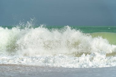 Big waves and surf on a sandy tropical beach