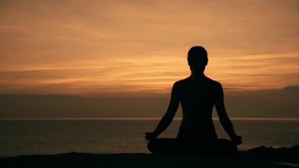 Silhouette einer meditierenden jungen Frau, die in Lotusposition auf einem Felsen am Meer vor dem Hintergrund der Morgendämmerung sitzt