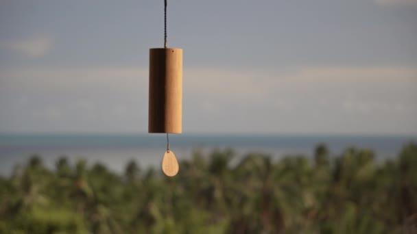Vítr zvonění v domě na pozadí tropických stromů, modrá obloha a moře v letním dni
