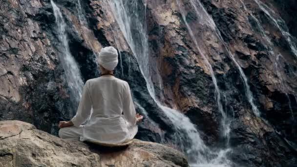Junge erwachsene Frau in weißen Kleidern sitzt auf einem Felsen vor dem Hintergrund eines Wasserfalls und praktiziert Yoga