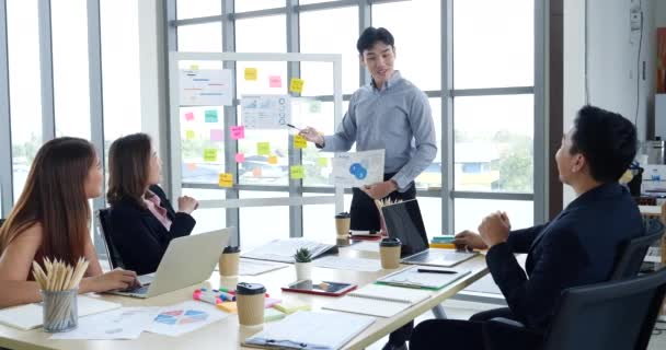 Happy business people meeting present graph chart investment, business data in meeting room. Group of business people meeting in conference room. Asian businessman speech, present teamwork partnership