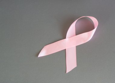Pink ribbon to raise awareness of breast cancer, the image on a gray background, copy space