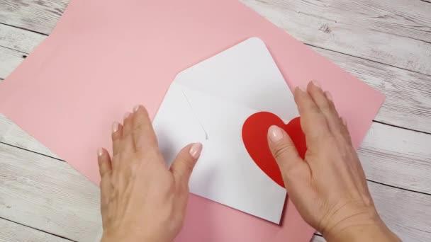 Női kezek nyissa ki a fehér borítékot, és vegye ki a Valentin-napi ünnepre egy piros szív alakú Valentin-kártyát. Rózsaszín háttér, romantikus nyilatkozat a szerelem