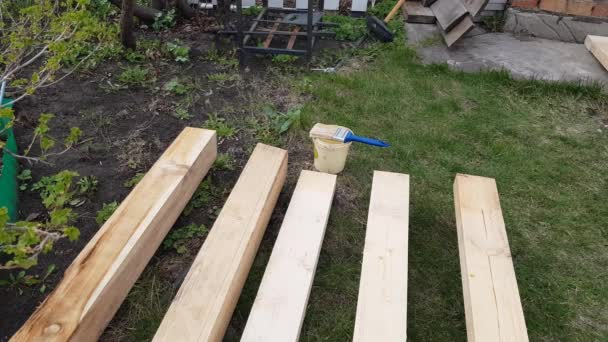 Fa deszkák, fűrészáru, ipari fa közelsége a füvön. Lábak egy ember készül festeni fa deszkák kész építési egy vidéki ház 4K videó