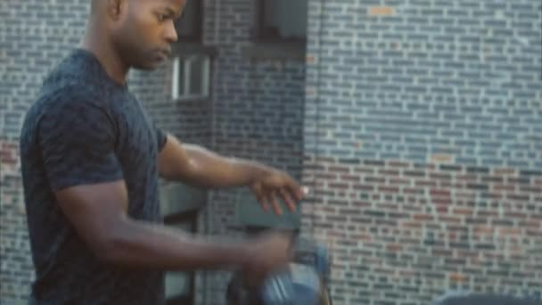 Jamaican male performing kettlebell clean and press