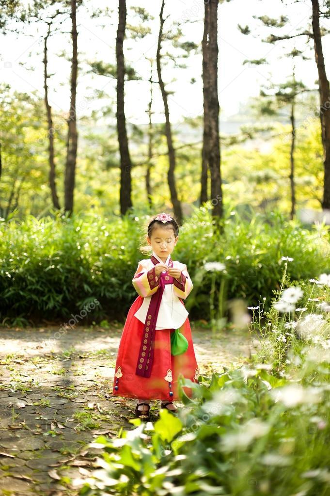 Korean child wearing a Traditional Hanbok, flower garden