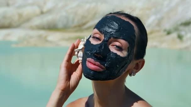Žena s černý jíl obličeje masku. Krása, Wellness. Venkovní wellness
