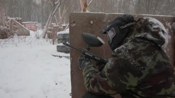 Bližší pohled paintball zbraň, při pohledu na cíl. Muž střílí na cíl
