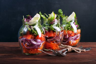 Salad with arugula, carrots, tomatoes, purple onion and lime in a glass jar. The concept of wholesome food home cooking, which you can take with you to work in a glass jar. Vegetarian salad. Useful dietary meal.