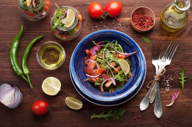 The concept of a healthy diet. Light salad of arugula, tomato, purple onion and lime, which you can take with you to work in a glass jar. Useful and tasty take away food.