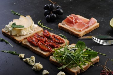 The concept of Italian food. Sandwiches with various fillings, such as arugula, dried tomatoes, pear, blue cheese and ham on dark background