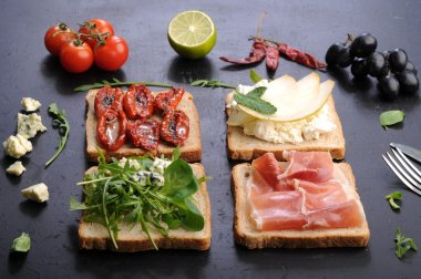 Sandwiches with various fillings on a black background. Sandwiches with ham, blue cheese, arugula and sun-dried tomatoes.