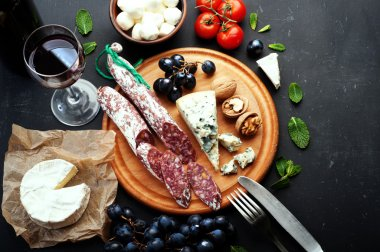Italian food concept. Jerked sausage, various cheeses, blue grapes, vegetables and fruits on a dark background.