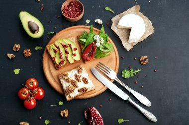 Sandwiches with a variety of toppings such as arugula, dried tomatoes, soft cheese, blue cheese, nuts and avocados on a dark background. The concept of healthy vegetarian food.