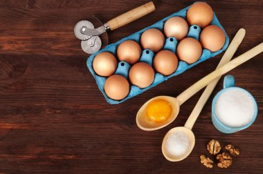 Ingredients for cooking, such as sugar, eggs and flour on a dark wooden background. Background for the recipe.