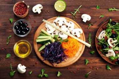 The concept of dietetic vegetarian food. Bright juicy shredded vegetables, such as carrots, purple cabbage, mushrooms and cucumbers, which lies on a circular wooden cutting board. Natural organic products, ready to eat