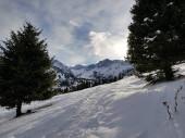 Krajina s mraky nad horami v zimě.