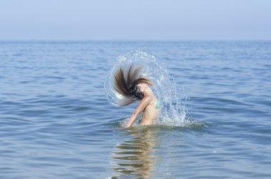 Beauty Model Girl Splashing Water with her Hair. Teen girl Swimming and splashing on summer beach over sunset. Beautiful Woman in Water. Summer holidays at sea