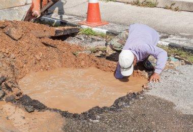 Male workers repair pipe water main broken