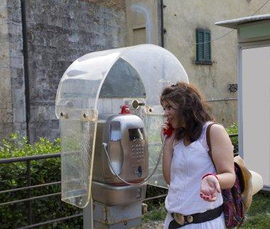Woman speaking in a public telephone